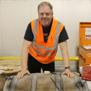 Shaun O Sullivan shows off his wandering barrel, filled and then left to age at the new 21A Facilities in San Leandro during the entire construction.  A liquid time capsule